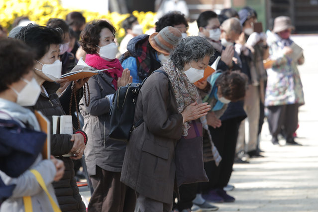 People wearing face masks to help curb the spread of the coronavirus pray during a service at the Chogyesa temple in Seoul, South Korea, Monday, October 19, 2020. South Korea on Monday began testing tens of thousands of employees of hospitals and nursing homes to prevent COVID-19 outbreaks at live-in facilities. (Photo by Ahn Young-joon/AP Photo)