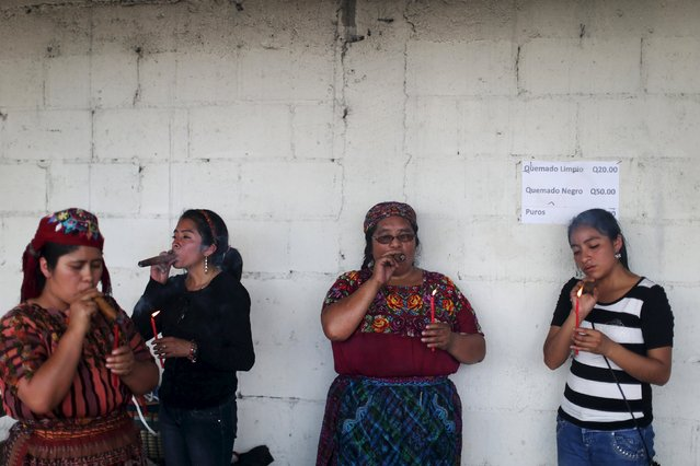 Women smoke tobacco outside the church of San Simon in Iztapa, in Chimaltenango, around 62 km (39 miles), from Guatemala City, October 28, 2015. (Photo by Jorge Dan Lopez/Reuters)