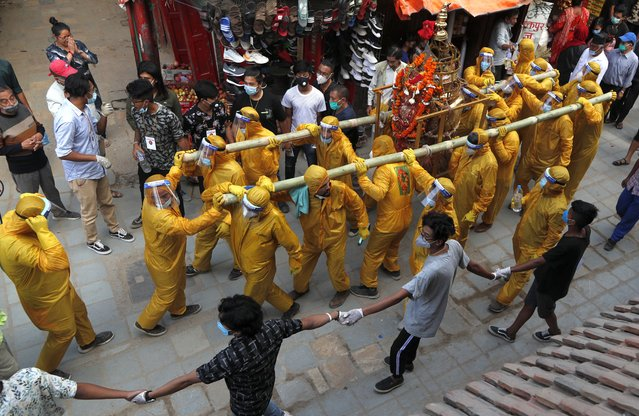 Nepalese devotees wearing protective gear as a precautionary measure against the coronavirus carry the chariot during Pachali Bhairav festival in Kathmandu, Nepal, Wednesday, October 21, 2020. The festival which is usually celebrated in the night time during Dashain festival was celebrated during the day because of the pandemic. (Photo by Niranjan Shrestha/AP Photo)