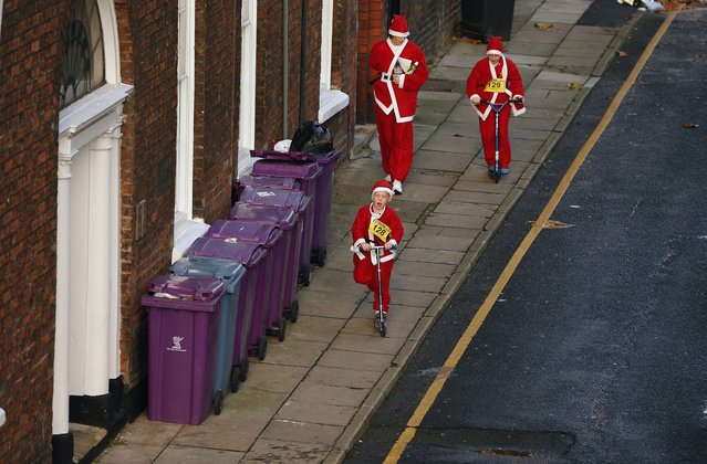 People dressed as Santa Claus walk down a road ahead of the start of the annual Santa Dash in Liverpool, northern England December 7, 2014. (Photo by Phil Noble/Reuters)