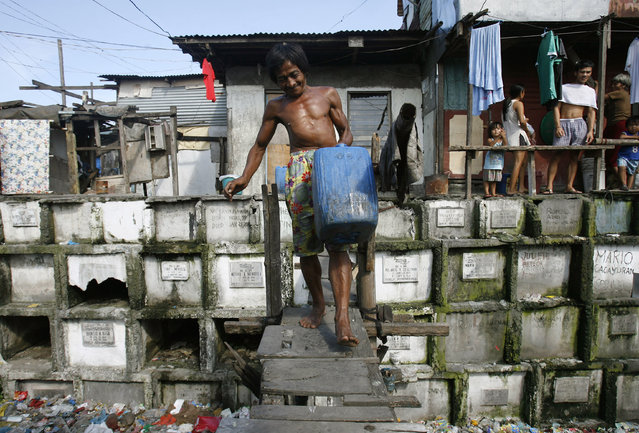 A man fetches water for his home inside a cemetery in Manila, October 21, 2008. (Photo by Cheryl Ravelo/Reuters)