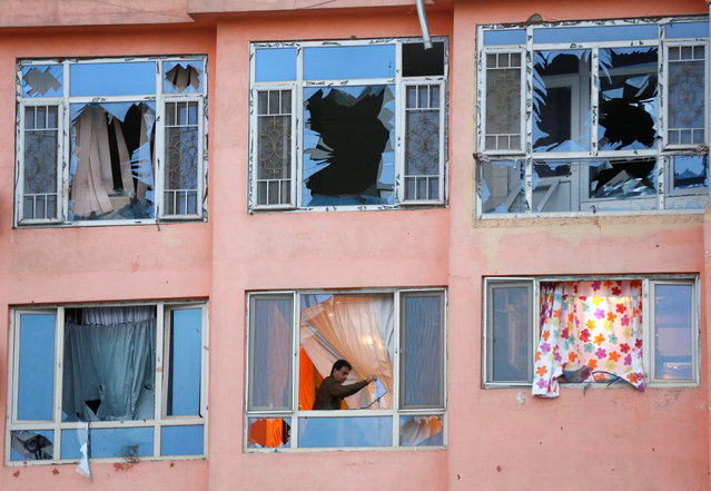 An Afghan man removes glasses from his apartment at the site of a suicide attack in Kabul, Afghanistan October 5, 2016. (Photo by Mohammad Ismail/Reuters)