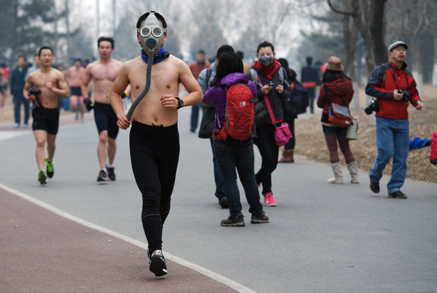 "A half-naked participant wears a gas mask as he takes part in the second ""Guangzhu (naked) Run"" on a winter morning at the Olympic Forest Park in Beijing, on February 24, 2013. About 100 people joined this event, which required them to run wearing only their underwear for 3.5 km (2.2 miles), as a way to promote environmentally-friendly lifestyles. (Photo by Reuters/China Daily /The Atlantic)"