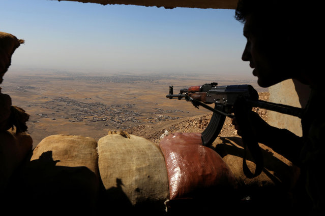Iraqi Kurdish Peshmerga fighters hold a position on the top of Mount Zardak, about 25 kilometres east of Mosul, on October 6, 2016. Mosul, Iraq's second city, was seized by the Islamic State (IS) group in 2014 after multiple Iraqi divisions collapsed in the face of a jihadist assault. But Baghdad is now planning, with help from a US-led coalition, a major operation to retake the city, which had a population of two million before the IS invasion. (Photo by Safin Hamed/AFP Photo)