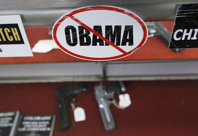A sticker is seen at the Rocky Mountain Guns and Ammo store in Parker, Colorado July 24, 2012. The killing of 12 people at a midnight screening of the new Batman movie in the Denver suburb of Aurora may spark a fresh round of soul-searching on America's relationship with guns but few predict any real change in the law. (Photo by Shannon Stapleton/Reuters)