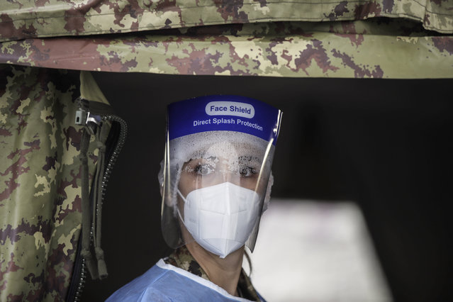 Army medical personnel, wearing a protective suit, works at a quick coronavirus testing area which was set up to ease the pressure on hospital emergency wards, following the surge of COVID-19 case numbers, in Milan, Italy, Friday, November 13, 2020. The central government has put under partial lockdown some regions where the rate of virus transmission is particularly high and hospitals are running out of staff or space for patients, including in Lombardy, the northern region where the pandemic first erupted in Italy in February. (Photo by Luca Bruno/AP Photo)