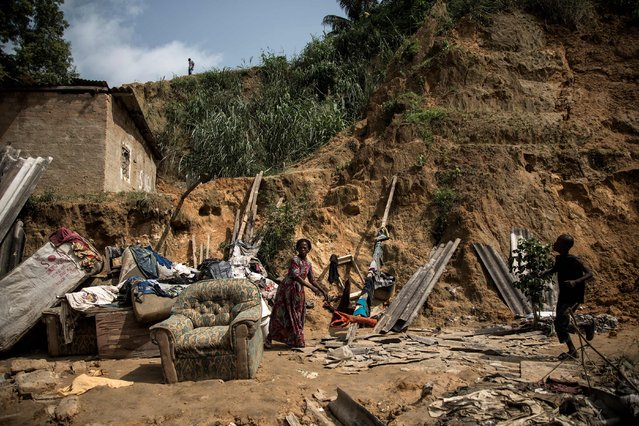A child walks past (R) and a woman stands among the remains of a landslide in Ngaliema district on January 5, 2018 in Kinshasa, Democratic Republic of Congo. Thirty-seven people died overnight when torrential rain and mudslides swept though shanty homes in Kinshasa. (Photo by John Wessels/AFP Photo)
