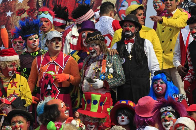 Clowns wait to pose for a group photo during their annual pilgrimage to the Basilica of Our Lady Guadalupe to pay homage to the Virgin of Guadalupe in Mexico City December 16, 2014. (Photo by Carlos Jasso/Reuters)