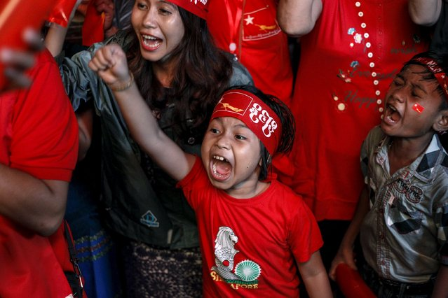 Supporters celebrate as they watch official results from the Union Election Commission on an LED screen in front of the National League for Democracy Party (NLD) head office in Yangon, November 9, 2015. (Photo by Soe Zeya Tun/Reuters)