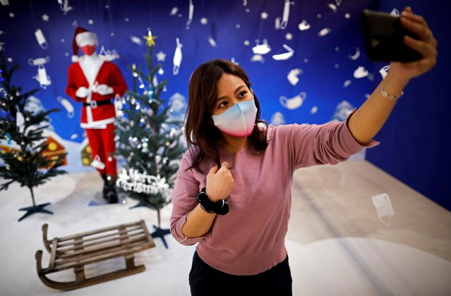 A woman tries to take selfie photos in front of a photo spot featuring Christmas season scene and masks at Tokyo Mask Land, a face-mask theme exhibition and its speciality shop, amid the coronavirus disease (COVID-19) outbreak, in Yokohama, Japan on December 1, 2020. (Photo by Issei Kato/Reuters)