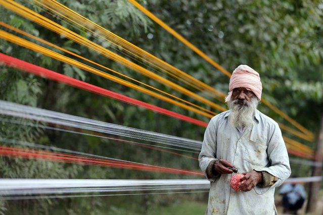 "An Indian worker makes a roll of the kite thread being prepared on a roadside on the outskirts of Amritsar, India, 24 November 2020. The kite string or the ""Dor"", in the local language, is made of crushed glass, glue, colors, and egg to make it strong enough to hold the kite. With the onset of the winter season, kite flying enthusiasts especially in northern Punjab, ranging from children to aged people, start flying kites as a leisure activity from their homes' rooftops and from open spaces, enjoying warmth of the winter sun at the same time. Kite flying season peaks in Amritsar on Lohri festival which marks the culmination of winter and is celebrated in the month of January every year. (Photo by Raminder Pal Singh/EPA/EFE)"