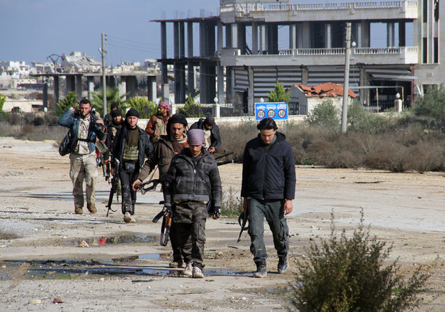 Rebel fighters walk around al-Hamidiyeh base, one of two military posts they took control of from forces loyal to Syria's President Bashar al-Assad in the northwestern province of Idlib, December 15, 2014. (Photo by Reuters/Stringer)