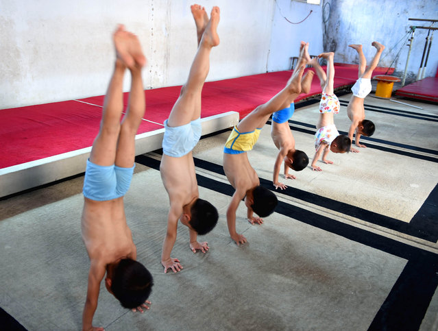 Performing handstands. (Photo by ChinaFotoPress/ChinaFotoPress via Getty Images)