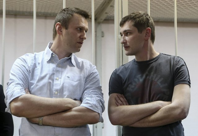 Russian opposition leader and anti-corruption blogger Alexei Navalny (L) and his brother and co-defendant Oleg attend a court hearing in Moscow December 30, 2014. A Russian court ruled on Tuesday to give Kremlin critic Alexei Navalny a suspended sentence for embezzling money but jailed his brother for three and a half years in a case seen as part of a campaign to stifle dissent. (Photo by Sergei Karpukhin/Reuters)