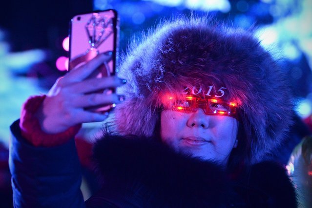 A woman uses her mobile phone to take a photo during the New Year's Eve countdown event in front of Beijing's National Stadium, Known as the Bird's Nest in Beijing on December 31,2014. Beijing is bidding to host the 2022 Winter Olympic Games, with a decision on the winning city to be made in July 2015. (Photo by Wang Zhao/AFP Photo)