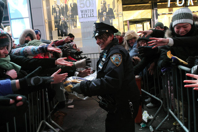 NYPD police officer Bedi, center, distributes gloves, given to her by the Time Square Alliance, to revelers in New York's Times Square during the New Year's Eve festivities Wednesday, December 31, 2014. (Photo by Tina Fineberg/AP Photo)