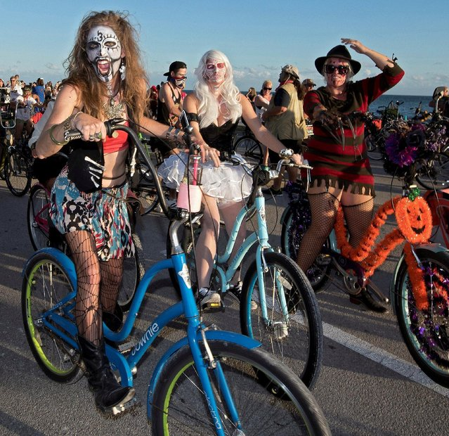 A portion of some 8,000 participants pedal past the Atlantic Ocean on South Roosevelt Boulevard during the Zombie Bike Ride as part of annual Fantasy Fest costuming and masking festival in Key West, Florida, U.S. October 23, 2016. (Photo by Rob O'Neal/Reuters/Florida Keys News Bureau)