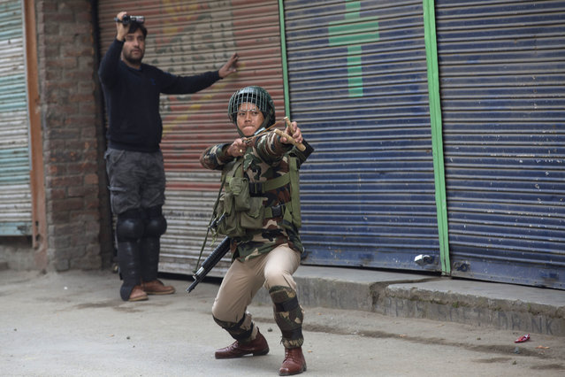 An Indian paramilitary solider uses a sling shot as a policeman in plainclothes takes a video of Kashmiri protesters in Srinagar, Indian controlled Kashmir, Friday, November 20, 2015. Police fired teargas and rubber bullets to disperse Kashmiris who gathered after Friday afternoon prayers to protest against the arrest of separatist leaders and civilians. (Photo by Dar Yasin/AP Photo)