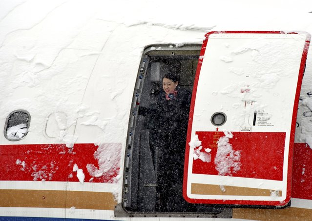 A flight attendant is seen in an opened hatch of a passenger plane docked at the Beijing Capital International Airport, amid heavy snowfall, in Beijing, China, November 22, 2015. Snowstorms have swept across a vast area of north China, disrupting traffic, grounding flights and slowing bullet trains in Beijing, Tianjin, Hebei Province and the Inner Mongolia Autonomous Region, while nearly 300 flights were cancelled at Beijing Capital International Airport, Xinhua News Agency reported. (Photo by Reuters/Stringer)