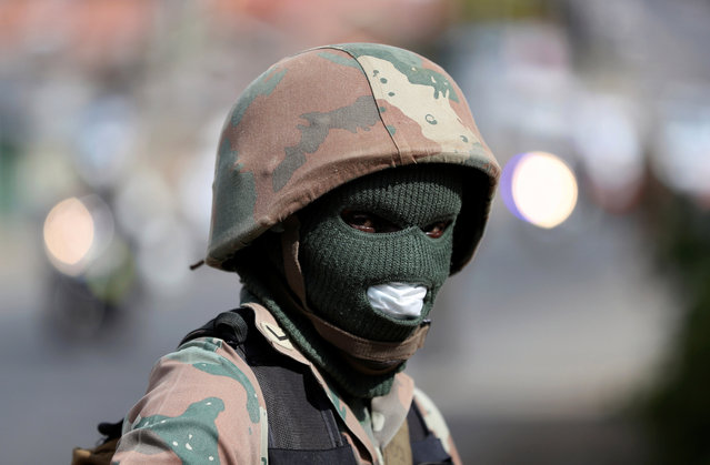 A member of the South African National Defence Force looks on during a patrol in an attempt to enforce a 21 day nationwide lockdown, aimed at limiting the spread of coronavirus disease (COVID-19), in Alexandra township, South Africa, March 28, 2020. (Photo by Siphiwe Sibeko/Reuters)