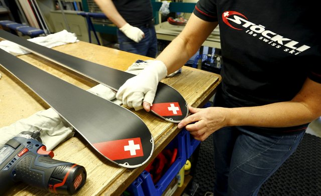 An employee places an edge protector on a ski at the plant of Swiss ski manufacturer Stoeckli in Malters, Switzerland November 25, 2015. (Photo by Arnd Wiegmann/Reuters)