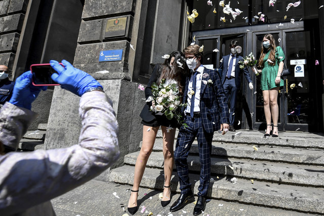A just married couple is celebrated by friends as they leave the registry offices after the civil ceremony in Milan, Italy, Friday, May 8, 2020. The municipality of Milan restarted celebrating civil marriages Thursday, as the city is slowly returning to life after the long shutdown due to the coronavirus outbreak. Access to the ceremony is only allowed for best men. (Photo by Claudio Furlan/LaPresse via AP Photo)