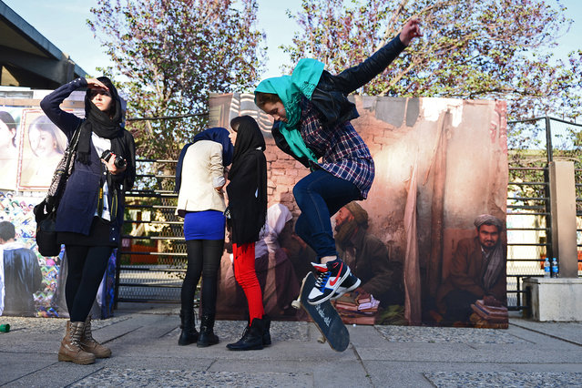 A foreign youth pops an ollie on her skateboard as Afghan youths gather for The Sound Central Festival at the French Cultural Center in Kabul, on May 2, 2013. The Sound Central Festival, now on its second year, is the only event of its kind that takes places in Afghanistan, where music was banned by the Taliban until the end of 2001. (Photo by Massoud Hossaini/AFP Photo)
