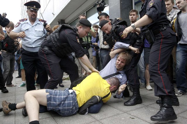 """Policemen break up a fight between a gay rights activist and an anti-gay rights activist (in yellow) during a protest against a proposed new law termed by the State Duma, the lower house of Parliament, as """"against advocating the rejection of traditional family values"""" in central Moscow June 11, 2013. (Photo by Maxim Shemetov/Reuters)"""