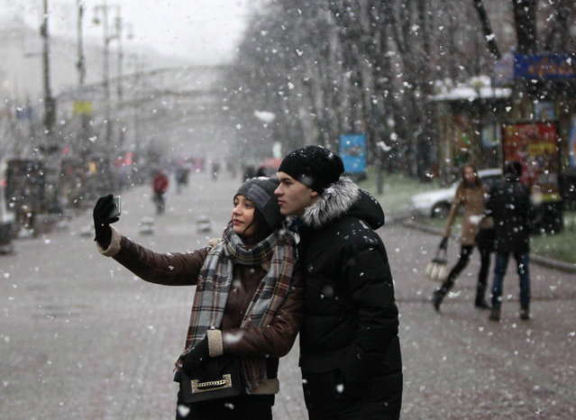 Young couple pose for a selfie under falling snow in downtown Kiev, Ukraine, Tuesday, December 1, 2015.  The temperature in the Ukrainian capital is about 0 degrees Celsius (32 degrees Fahrenheit) on Tuesday. (Photo by Sergei Chuzavkov/AP Photo)
