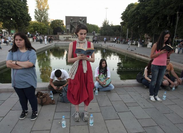 In this photo taken Tuesday, June 18, 2013, a woman stands in a silent protest as others read at Kizilay Square in Ankara, Turkey. After weeks of sometimes-violent confrontation with police, Turkish protesters have found a new form of resistance: standing still and silent. (Photo by AP Photo)