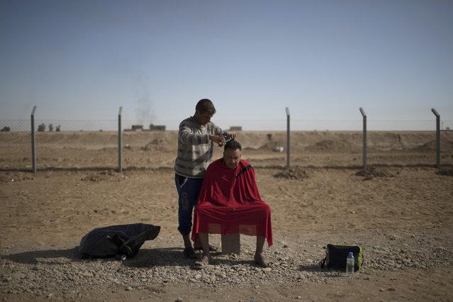 A displaced man has his hair cut at Jedaa camp in Qayara, south of Mosul, Iraq, Thursday, November 3, 2016. (Photo by Felipe Dana/AP Photo)
