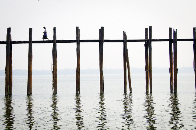 """Daybreak in Mandalay"". A moment of calm: a man walks across U-Bein Bridge before the onslaught of morning foot-traffic. Location: Mandalay, Myanmar. (Photo and caption by Jocelyn Voo/National Geographic Traveler Photo Contest)"