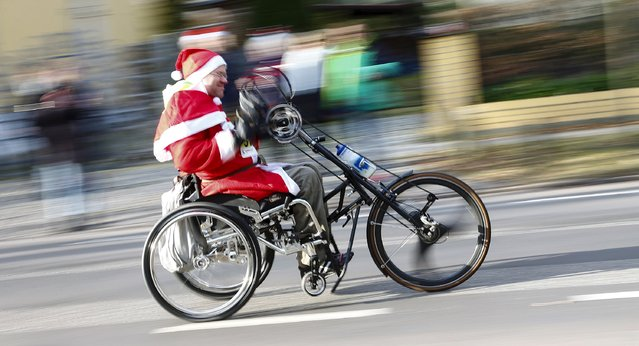 A handicapped man dressed as Father Christmas participates in the Nikolaus Lauf (Santa Claus Run) in the east German town of Michendorf, southwest of Berlin, Germany, December 6, 2015. (Photo by Hannibal Hanschke/Reuters)
