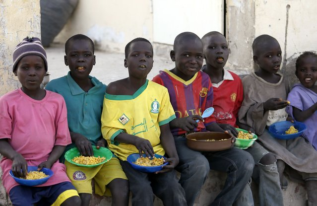 Children displaced as a result of Boko Haram attacks in the northeast region of Nigeria, sit in a row to eat a meal at a camp for internally displaced persons (IDP) in Yola, Adamawa State January 13, 2015. (Photo by Afolabi Sotunde/Reuters)