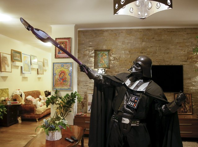 Darth Mykolaiovych Vader, who is dressed as the 'Star Wars' character Darth Vader, poses for a picture with a vacuum cleaner as he cleans his apartment in Odessa, Ukraine, December 2, 2015. (Photo by Valentyn Ogirenko/Reuters)