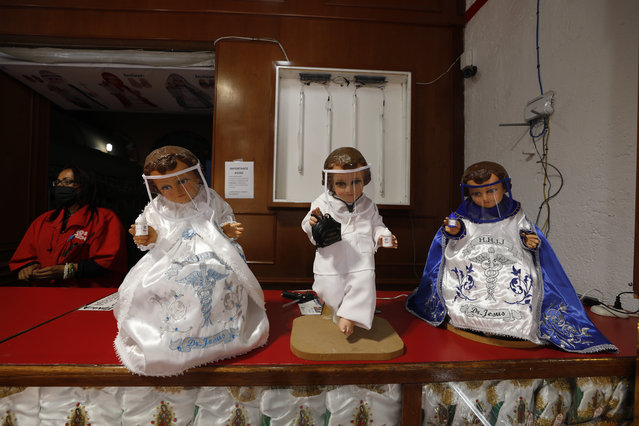 Figurines of the Baby Jesus, one dressed as a COVID-19 doctor, are displayed in store specializing in Baby Jesus outfits and accessories and face shields, in Mexico City, Friday, December 4, 2020. Amid a surge in COVID-19 cases and hospitalizations, Mexico's capital is once again calling on people to stay at home as much as possible. (Photo by Rebecca Blackwell/AP Photo)