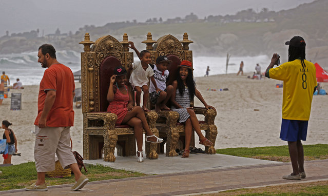 A family have their photo taken on two giant chairs that form part of a city art project at Camps Bay, near the city of Cape Town, South Africa, Saturday, January 24, 2015. (Photo by Schalk van Zuydam/AP Photo)