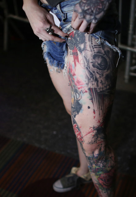 A woman shows her tattoo covered leg as she attends the annual Venezuela Tattoo International Expo in Caracas, Venezuela, Thursday, January 29, 2015. (Photo by Ariana Cubillos/AP Photo)