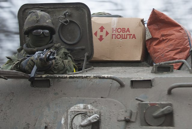 A Ukrainian serviceman holds his position in an APC near Artemivsk, eastern Ukraine, Thursday, February 5, 2015. Fighting between Russia-backed separatists and Ukrainian forces in eastern Ukraine surged in January, raising the death toll to over 5,300 people killed since April. In a new push for peace, the leaders of France and Germany headed Thursday to Kiev and Moscow with a proposal to end the fighting in eastern Ukraine. (Photo by Evgeniy Maloletka/AP Photo)