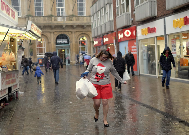 A woman walks with shopping during rainfall on Christmas Eve in Loughborough, Britain December 24, 2015. (Photo by Darren Staples/Reuters)