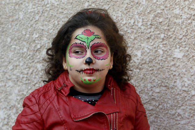 An internally displaced Christian girl, who has fled from Islamic State militants, stands against a wall with her face painted, at a church in Baghdad November 20, 2015. (Photo by Khalid al-Mousily/Reuters)