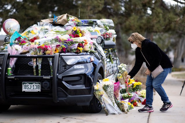 Karla Bielanski places flowers on the car of Officer Eric Talley, who was killed yesterday during a mass shooting in King Soopers grocery store, at Boulder Police Department, in Boulder, Colorado, U.S., March 23, 2021. (Photo by Alyson McClaran/Reuters)