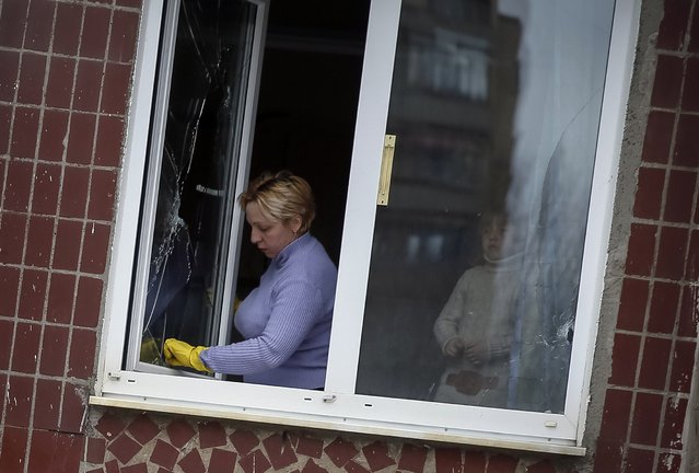 A woman removes glass from the broken window of her home in the town of Kramatorsk, eastern Ukraine February 10, 2015. (Photo by Gleb Garanich/Reuters)