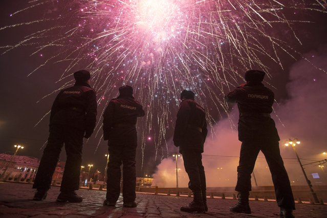 Police officers photograph fireworks as they guard Red Square in Moscow, Russia, in Moscow, Russia, Friday, January 1, 2016. Putin is using his New Year's message to commemorate both the country's current fight in Syria and the battles of World War II seven decades ago. The recorded message was being televised just before midnight Thursday in each of Russia's nine time zones. (Photo by Denis Tyrin/AP Photo)