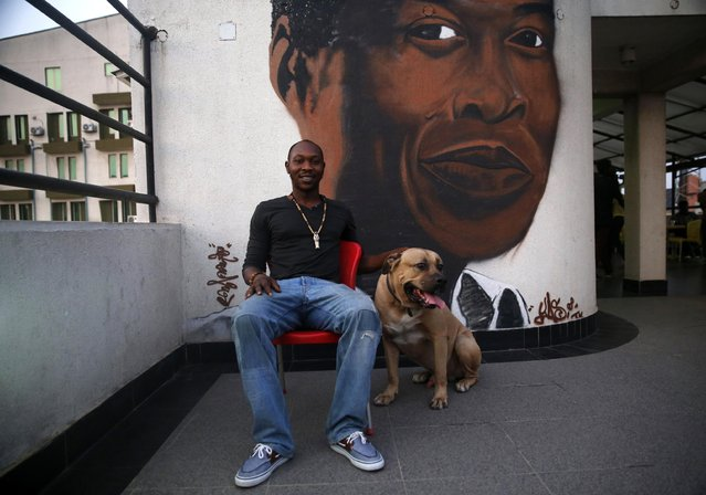 Afrobeat musician Seun Anikulapo-Kuti, 32, an ethnic Yoruba, poses with his dog on an open terrace at the Fela museum in Lagos February 1, 2015. Anikulapo-Kuti is the son of Nigeria's music legend Fela Kuti. He believes Boko Haram is not a new kind of revolutionary group but an entity created for some kind of political disturbances in Nigeria. (Photo by Akintunde Akinleye/Reuters)