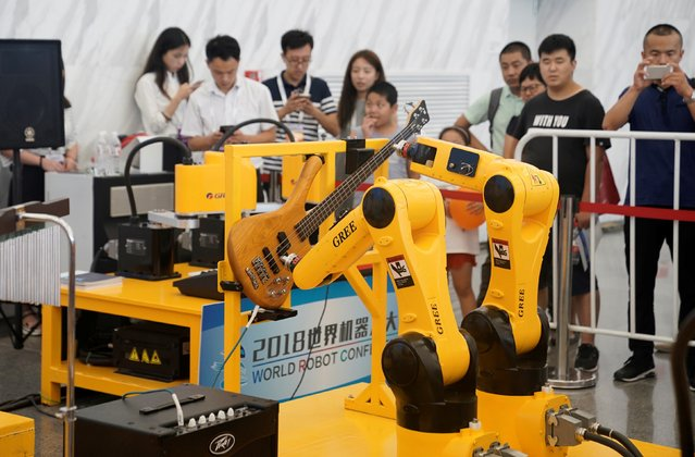 A robotic arm plays the guitar at Zhuhai Gree Electric's booth at the World Robot Conference (WRC) in Beijing, China on August 15, 2018. (Photo by Jason Lee/Reuters)