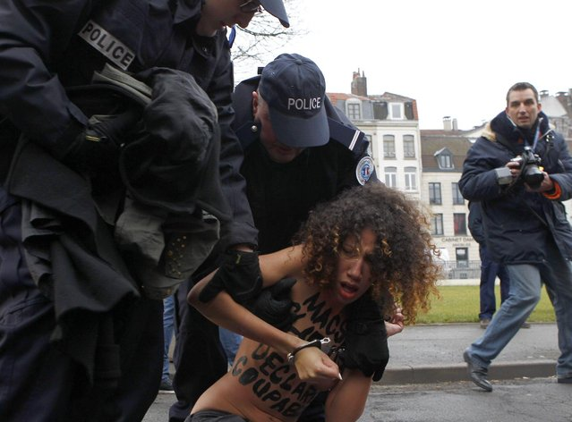 A FEMEN activist is held down by police officers as she protests Tuesday, February 10, 2015 in front of the Lille courthouse in Lille, northern France, where Dominique Strauss-Kahn goes on trial for s*x charges in France. The former head of the International Monetary Fund, whose career went down in flames amid accusations of sexually assaulting a hotel maid in New York. (Photo by Michel Spingler/AP Photo)