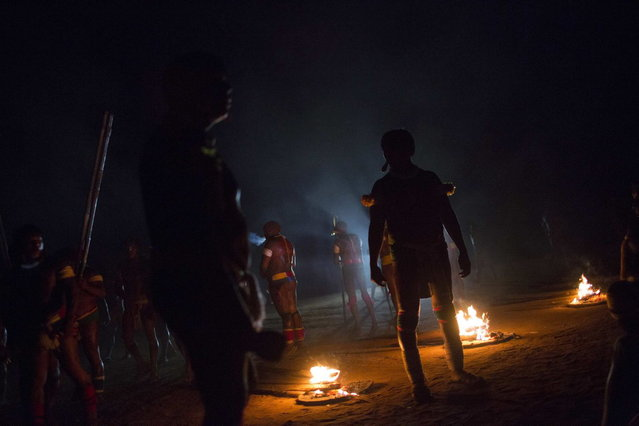 """Waura Indians participate in the fire ritual during this year's """"quarup"""", a ritual held over several days to honour in death a person of great importance to them, in Xingu National Park, Mato Grosso State, August 24, 2013. This year the Waura tribe honoured their late cacique (chief) Atamai, who died in 2012, for his work creating the Xingu Park and his important contribution in facilitating communication between white Brazilians and Indians. (Photo by Ueslei Marcelino/Reuters)"""