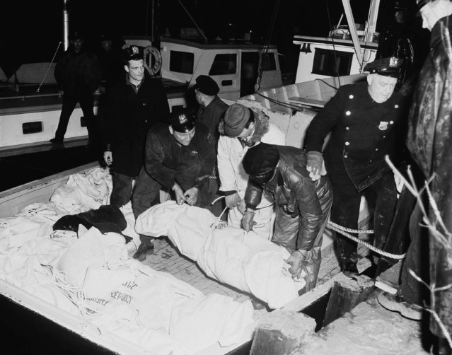 Police emergency squad members hoist body of victim in crash of American Airlines Plane late on February 3, 1959 to New York Pier. Other bodies plucked from the strong icy currents of the east river lie on stern of the police launch. Plane, carrying 72, smashed to pieces on water as it tried to land in Fog and drizzle at La Guardia Field, New York. (Photo by AP Photo)