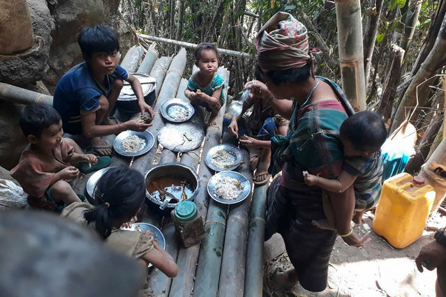 This undated handout from the KNU Doo Pla Ya District released to AFP on April 8, 2021 shows Karen villagers eating in the KNU Brigade 5 region in Myanmar's Karen state, after air strikes in the area following the February military coup. (Photo by Handout/KNU DOO PLA YA DISTRICT/AFP Photo)